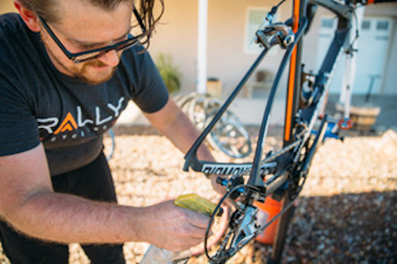 Zane Freebairn cleans and inspects the bikes after a long, dusty training ride.